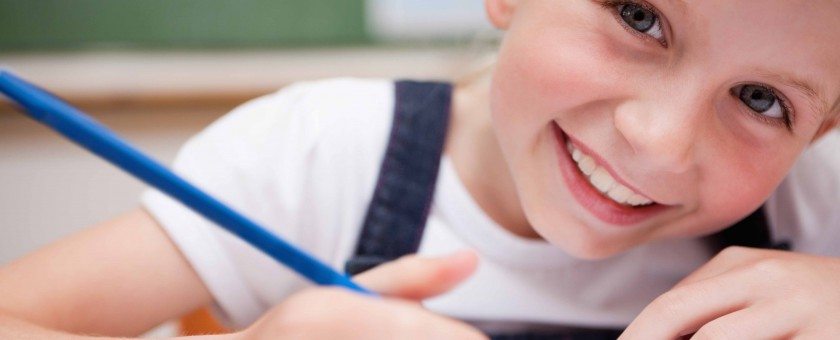 Close up of a smiling schoolgirl writing something
